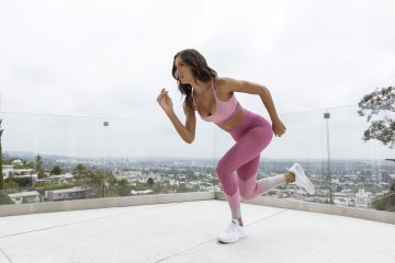 A girl working out on a roof doing cardio.