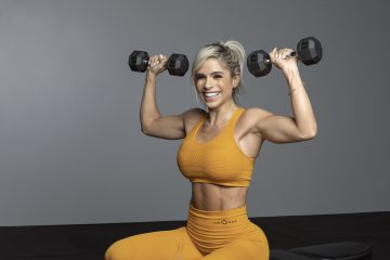 A woman doing overhead dumbbell presses.